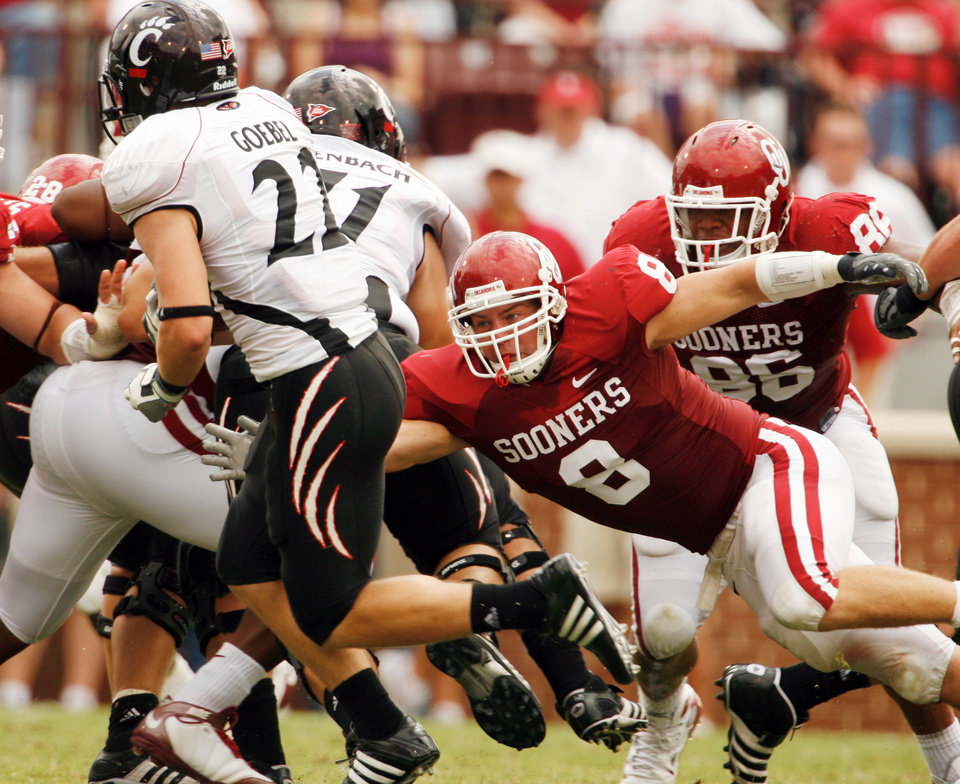 Photo - Ryan Reynolds (8) tackles John Goebel behind the line in the first half during the college football game between the University of Oklahoma (OU) and Cincinnati at Gaylord Family -- Oklahoma Memorial Stadium in Norman, Okla., Saturday, September 6, 2008.   BY STEVE SISNEY, THE OKLAHOMAN ORG XMIT: KOD