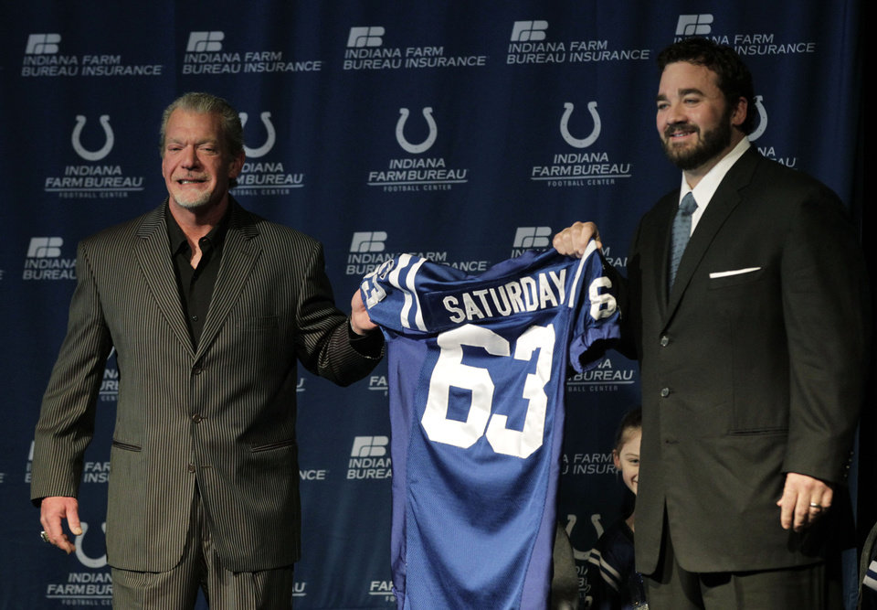 Photo - Jeff Saturday, right, accepts a jersey from Indianapolis Colts owner Jim Irsay during a news conference before signing a one-day contract in order to retire as a Colts player, Thursday, March 7, 2013, in Indianapolis. Saturday spent 13 seasons in Indianapolis before signing with Green Bay last year. (AP Photo/AJ Mast)