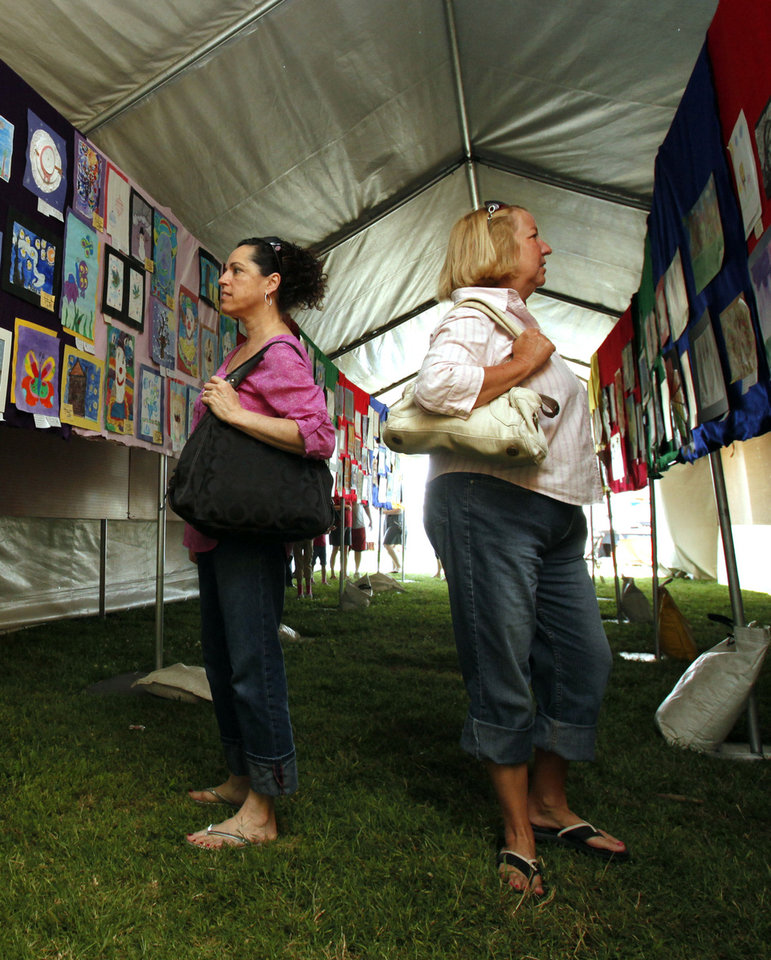 Sandy Terry, left, and Liz Tiffany study artwork posted in the children's art tent at the annual May Fair Festival at Andrews Park in Norman. PHOTO BY STEVE SISNEY, THE OKLAHOMAN <strong>STEVE SISNEY</strong>