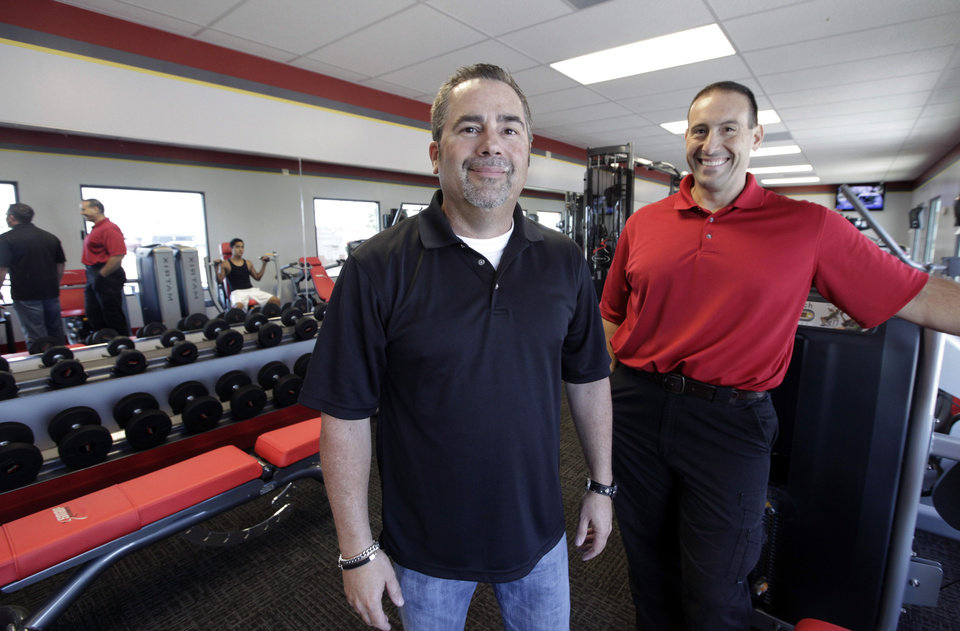 Photo -   ADDS FULL NAME OF GYM - In this June 14, 2012, photo, Gary Findley, Chief Operating Officer of Snap Fitness, left, and gym manager Rick Limitone, pose for a photo at Snap Fitness Rolling Strong Gym, a truck stop gym in Dallas. From trucking companies embracing wellness and weight-loss programs to gyms being installed at truck stops, momentum has picked up in recent years to help those who make their living driving big rigs get into shape. (AP Photo/LM Otero)