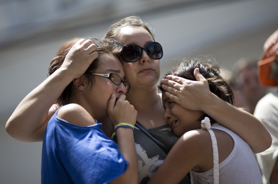 Photo - Girls cry in front of a makeshift memorial outside the Kiss nightclub where a fire killed over 230 people in Santa Maria, Brazil, Tuesday, Jan. 29, 2013. The repercussions of a tragic nightclub fire in southern Brazil widened Tuesday as mayors around the country cracked down on such venues in their own cities and investigators searched two other nightspots owned by a partner in the club that caught ablaze. Most of the dead were college students 18 to 21 years old, but they also included some minors.  (AP Photo/Felipe Dana)
