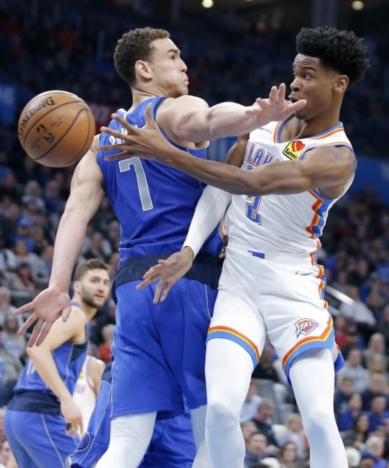 Photo -  Oklahoma City's Shai Gilgeous-Alexander, right, passes the ball around Dallas' Dwight Powell during Tuesday night's game at Chesapeake Energy Arena. [Bryan Terry/The Oklahoman]