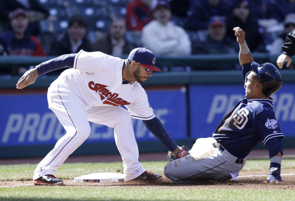 Photo - San Diego Padres' Everth Cabrera, right, is caught stealing third base as Cleveland Indians' Mike Aviles makes the tag in the third inning in the second game of a baseball doubleheader on Wednesday, April 9, 2014, in Cleveland. (AP Photo/Tony Dejak)