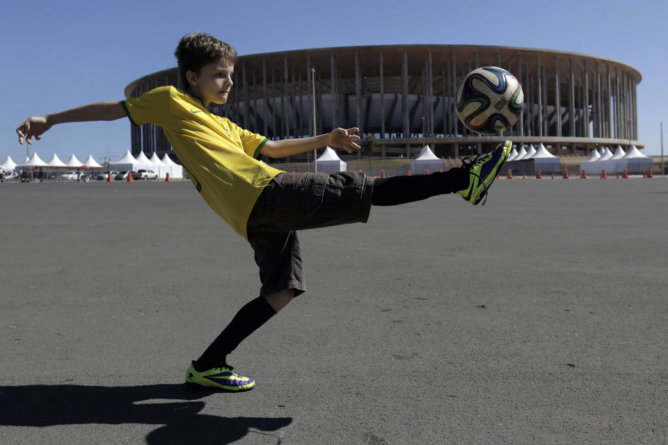 Photo - Lucas Zanatta, 10, plays with a soccer ball outside the National Stadium after visiting the official World Cup trophy on exhibit at the stadium in Brasilia, Brazil, Wednesday, May 28, 2014. Brasilia is one of the host cities for the 2014 World Cup in Brazil. (AP Photo/Eraldo Peres)