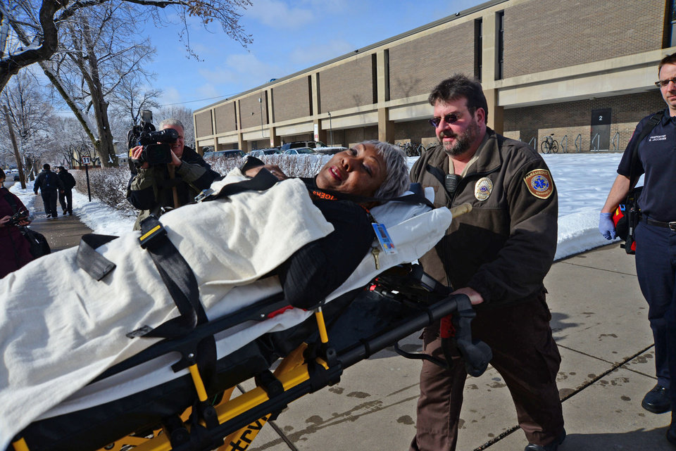 Photo - Emergency personnel brings an injured person out on a stretcher after a fight brought ambulances and police to the South High School in Minneapolis on Thursday, Feb. 14, 2013. The school is on lockdown after a food fight got out of hand and turned into a real fight. Minneapolis police were called after the fight broke out during third-period lunch around 12:45 p.m. Thursday. The fight lasted 15 minutes. The school says staff members responded immediately and took security steps. Teaching continues as usual during the lockdown, but students will remain in their classrooms during class. South will remain on lockdown until further notice.(AP Photo/The Star Tribune, Richard Sennott)  MANDATORY CREDIT; ST. PAUL PIONEER PRESS OUT; MAGS OUT; TWIN CITIES TV OUT