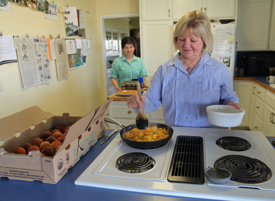 Photo - In this photo taken Friday, June 7, 2013 in Del Rey, Calif., farmer Marcy Masumoto sautes peaches in butter and brandy, while her daughter Nikiko makes multigrain waffles in the background. The recipe comes from the recently published Masumoto family cookbook, which the peach farming family wrote to tell the story of their farm and create a stronger link with peach eaters. (AP Photo/Gosia Wozniacka)