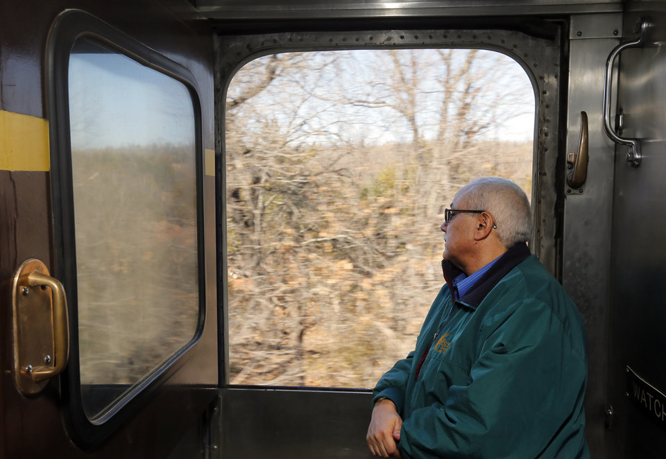 Photo - Jim Fetchero of Charlotte, N.C., watches the countryside go by on a demonstration ride of the Eastern Flyer passenger train from Sapulpa to the Oklahoma City metro area, Sunday, Feb. 23, 2014. Fetchero is the manager of passenger car operations for Iowa Pacific Holdings and rode the Eastern Flyer for fun before coordinating the movement of the cars to other destinations after the trip. Photo by Nate Billings, The Oklahoman