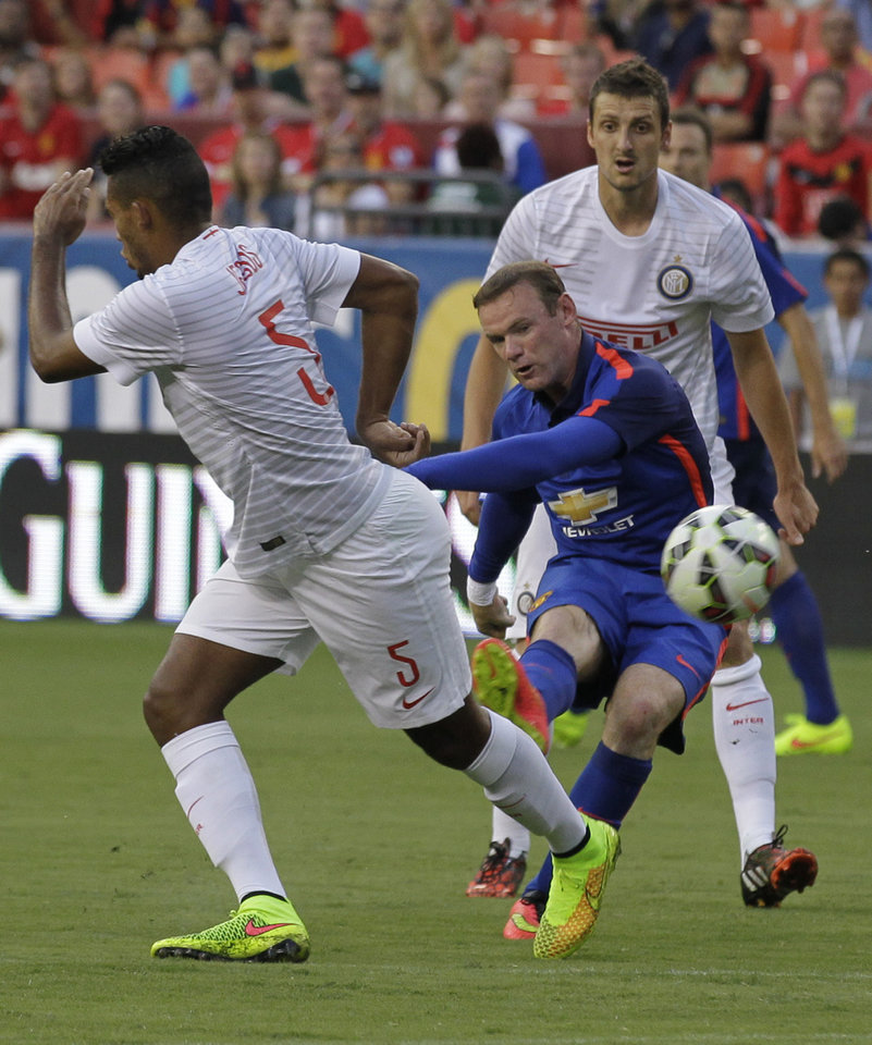 Photo - Manchester United's Wayne Rooney kicks the ball from between Inter Milan's Juan Jesus (5) and Inter Milan's Zdravko Kuzmanovic during the first half of a soccer game at  the 2014 Guinness International Champions Cup, Tuesday, July 29, 2014, in Landover, Md. Manchester United won 5-3 in a penalty kick shootout. (AP Photo/Luis M. Alvarez)