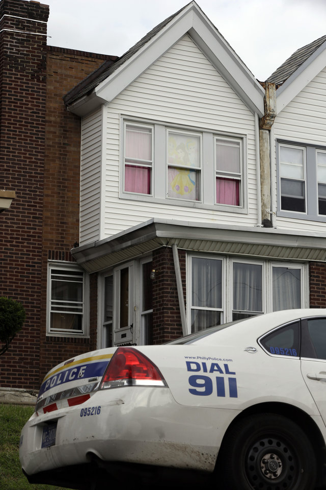 Photo - A police car sits in view of a decorated window in the home of a severely disabled 3-year-old girl who was pronounced dead at a nearby hospital, Monday, Sept. 9, 2013, in Philadelphia. Nathalyz Rivera, a twin, weighed just 11 pounds when she died and police in Philadelphia called her death a homicide. Police are searching for the girl's father, Carlos Rivera, after they said he left four other children in a relative's care and fled. (AP Photo/Matt Rourke)
