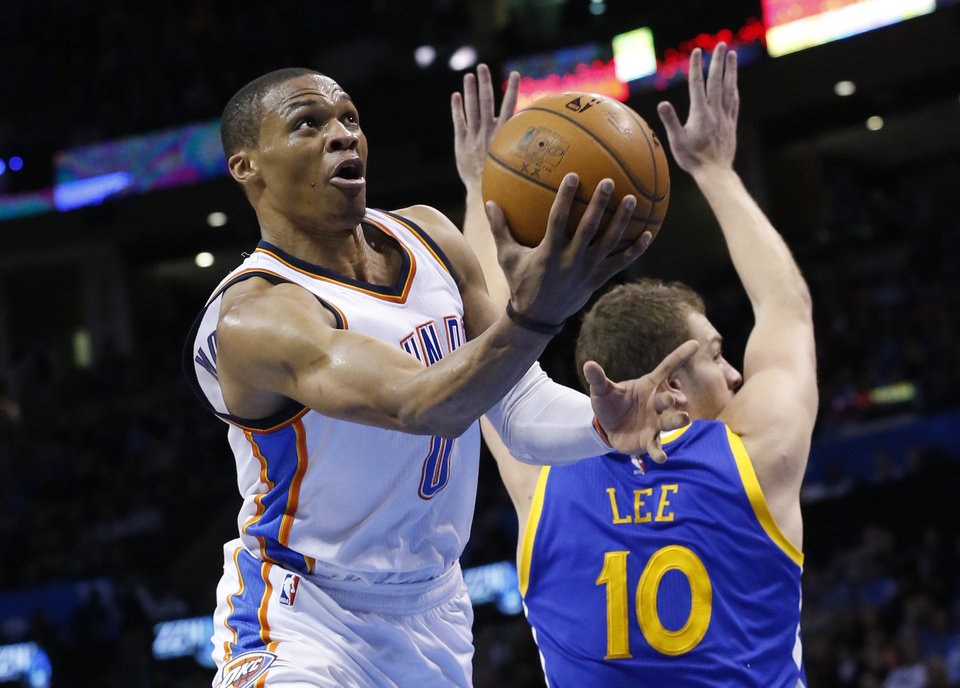 Photo - Oklahoma City Thunder guard Russell Westbrook (0) shoots in front of Golden State Warriors forward David Lee (10) during the fourth quarter of an NBA basketball game in Oklahoma City, Friday, Jan. 16, 2015. Oklahoma City won 127-115. (AP Photo/Sue Ogrocki)