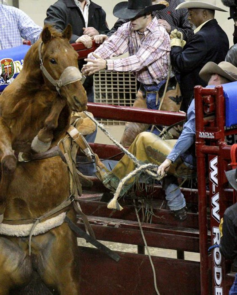 Photo -  A horse named Lone Wolf stands up and leaves Saddle Bronc rider Jon Tyson holding onto the fence  during the International Finals Rodeo at the State Fair Arena in Oklahoma City on Sunday, Jan. 16, 2011. Photo by John Clanton, The Oklahoman ORG XMIT: KOD