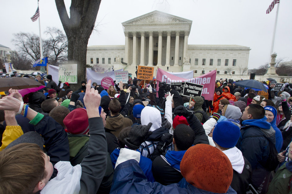 "FILE - In this Jan. 23, 2012, file photo, anti-abortion and abortion rights supporters stand face to face in front of the Supreme Court in Washington, Monday, Jan. 23, 2012, during the annual March For Life rally. There's been a lot of heated talk this year by Democrats contending that Republicans are waging a ""war on women."" That's hyperbole, retorts the GOP, but there are indeed stark differences between the two parties over these volatile issues. However, the next president _ Obama or Romney _ could have huge influence over the future of abortion policy if vacancies arise on the Supreme Court. For example, if two seats held by liberal justices were vacated and filled by Romney-nominated conservatives, prospects for a reversal of Roe v. Wade would increase. (AP Photo/Manuel Balce Ceneta, File)"