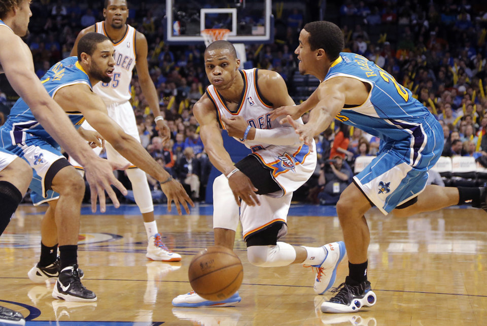 Photo - Oklahoma City Thunder's Russell Westbrook (0) passes the ball past New Orleans Hornets' Xavier Henry (4) and Brian Roberts (22) during the NBA basketball game between the Oklahoma City Thunder and the New Orleans Hornets at the Chesapeake Energy Arena on Wednesday, Feb. 27, 2013, in Oklahoma City, Okla. Photo by Chris Landsberger, The Oklahoman