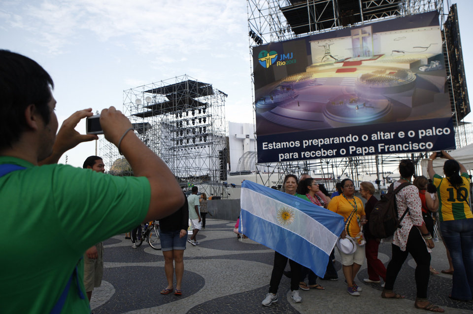 Argentinian pilgrims  takes pictutres in Rio de Janeiro Sunday July 21, 2013, with a giant television monitor erected for the papal visit in the background.    Pope Francis arrives July 22 in  Rio de Janeiro for the World Youth Day.(AP Photo/Jorge Saenz)