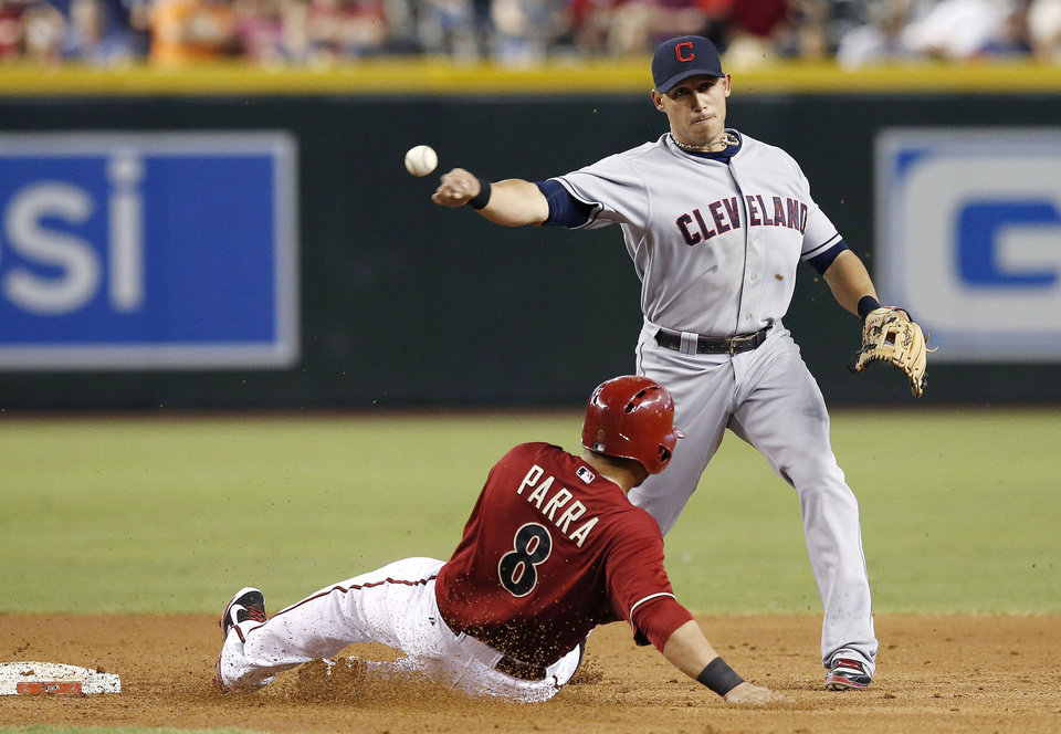 Photo - Cleveland Indians' Asdrubal Cabrera, right, throws to first after forcing out Arizona Diamondbacks' Gerardo Parra (8) during the first inning of a baseball game on Wednesday, June 25, 2014, in Phoenix. Miguel Montero was out at first on the double play. (AP Photo/Ross D. Franklin)