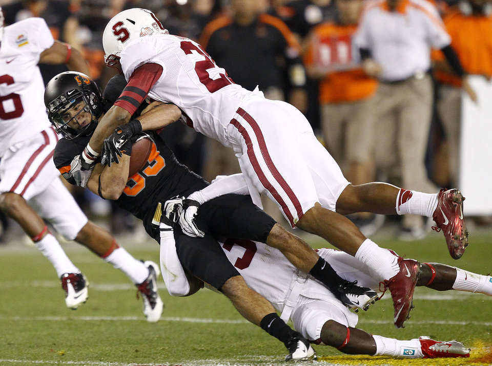 Photo - Oklahoma State wide receiver Colton Chelf, left, is tackled by Stanford safety Delano Howell, right, during the first half of the Fiesta Bowl NCAA college football game Monday, Jan. 2, 2012, in Glendale, Ariz. (AP Photo/Matt York)