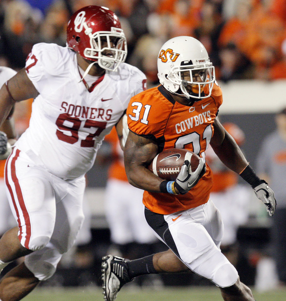 Photo - OSU's Jeremy Smith (31) gets past Jamarkus McFarland (97) in the first quarter during the Bedlam college football game between the University of Oklahoma Sooners (OU) and the Oklahoma State University Cowboys (OSU) at Boone Pickens Stadium in Stillwater, Okla., Saturday, Nov. 27, 2010. Photo by Nate Billings, The Oklahoman
