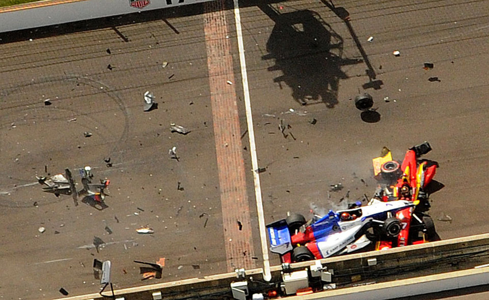 Photo - Mikhail Aleshin, of Russia, goes over the top of the car driven by Sebastian Saavedra, of Colombia, at the start of the inaugural Grand Prix of Indianapolis IndyCar auto race at the Indianapolis Motor Speedway in Indianapolis, Saturday, May 10, 2014.  (AP Photo/Indianapolis Star, Greg Griffo) NO SALES