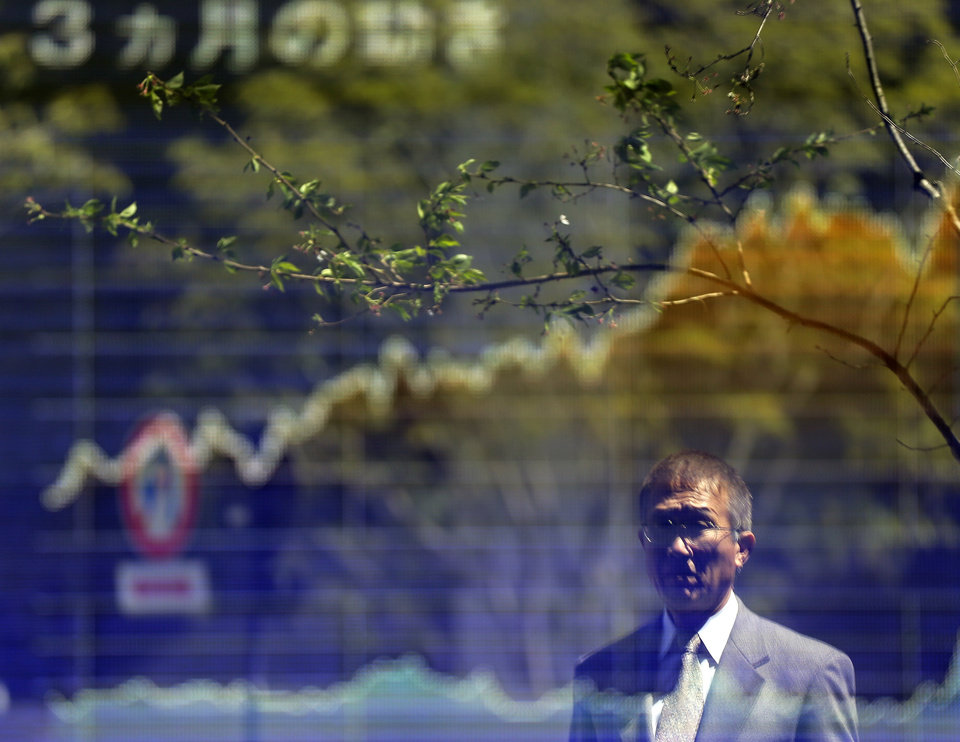 Photo - A man looks at an electronic stock board of a securities firm in Tokyo Monday, April 8, 2013 as Japan's Nikkei 225 index rose 258.31 points to 13091.95 at the morning session.  Asian stock markets were mixed Monday amid concerns about tensions on the Korean Peninsula, bird flu in China and a disappointing U.S. jobs report, although the Nikkei piled on more gains as the yen's dramatic fall boosted the country's powerhouse export sector. (AP Photo/Itsuo Inouye)