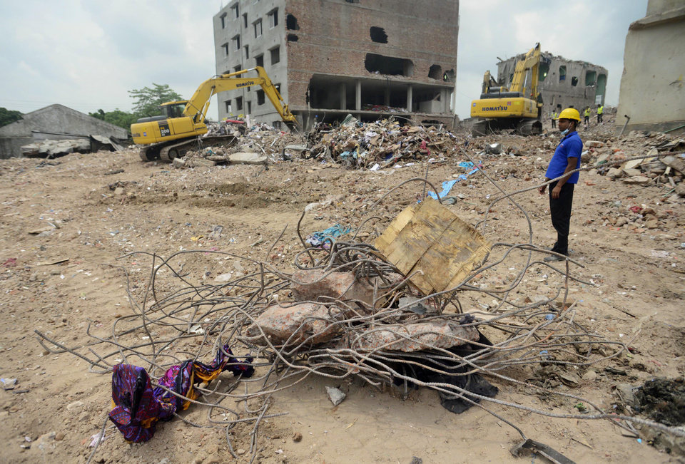 Photo - A Bangladeshi worker watches as he stands at the site of a garment factory that collapsed in Savar near Dhaka, Bangladesh, Friday, May 10, 2013. The death toll from a garment factory building that collapsed more than two weeks ago near the Bangladeshi capital soared past 1,000 on Friday, with no end in sight to the stream of bodies being pulled from the wreckage of the worst-ever garment industry disaster. (AP Photo/Ismail Ferdous)