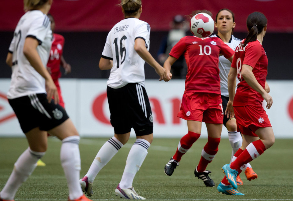 Photo - Canada's Jessie Fleming (10) is obscured by the ball as she gains control while Germany's Jennifer Cramer (16) and Nadine Kebler, back, watch during the first half of an international women's soccer game in Vancouver, British Columbia on Wednesday, June 18, 2014.  (AP Photo/The Canadian Press, Darryl Dyck)