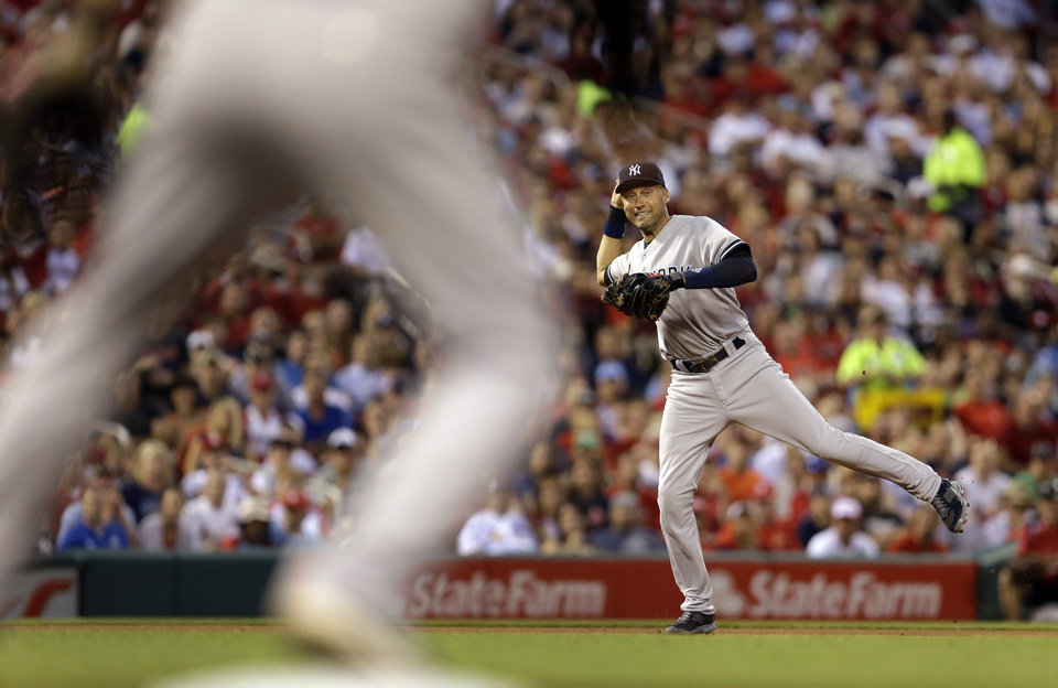 Photo - New York Yankees shortstop Derek Jeter, right, throws to first baseman Kelly Johnson during the third inning of a baseball game against the St. Louis Cardinals on Tuesday, May 27, 2014, in St. Louis. Johnson missed the throw, allowing Cardinals' Allen Craig to reach base and Matt Holliday to score. (AP Photo/Jeff Roberson)
