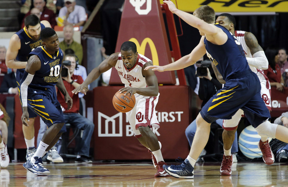 Photo - Oklahoma's Sam Grooms (1) takes off with the loose ball past West Virginia 's Dominique Rutledge (1) and Deniz Kilicli (13) during the first half of the college basketball game between the University of Oklahoma Sooners (OU) and the West Virginia University Mountaineers (WVU) at the Lloyd Noble Center on Wednesday, March 6, 2013, in Norman, Okla. Photo by Chris Landsberger, The Oklahoman