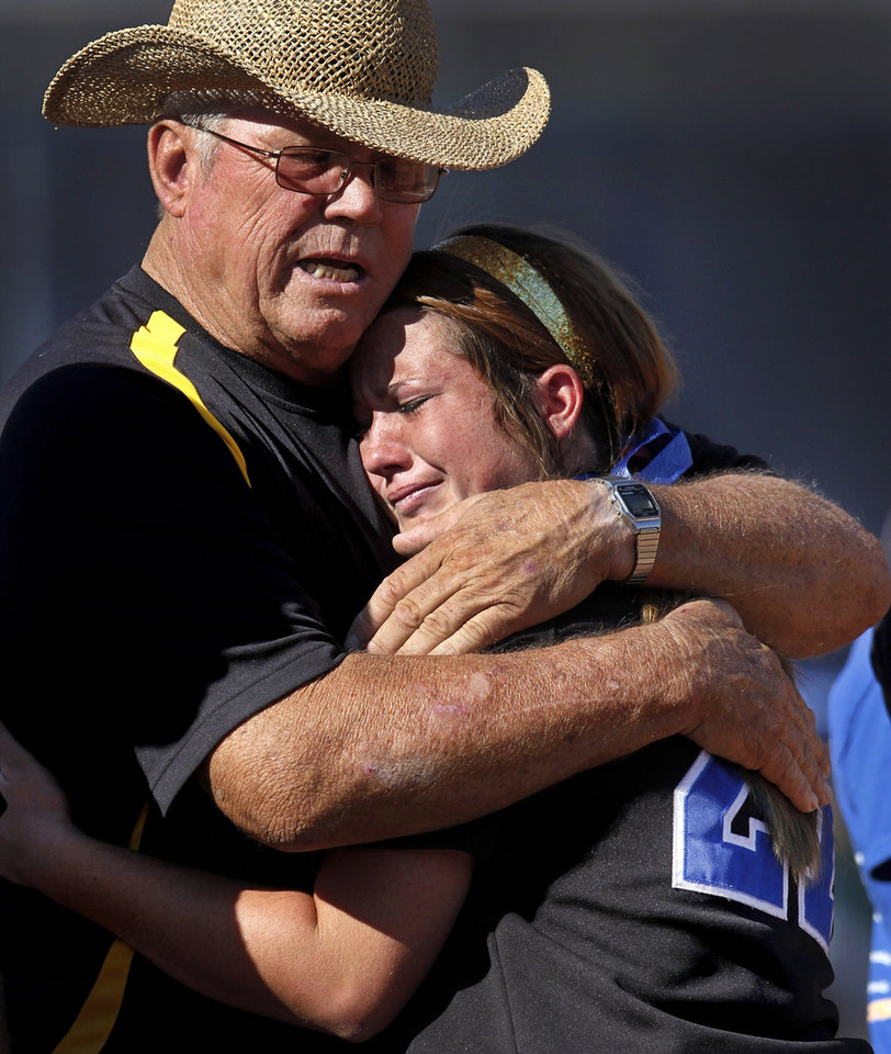 A tearful Courtney Anderson is consoled by assistant softball coach Walter Starry after she received her runner-up medal following their team's loss to Oologah. Class 4A high school championship softball game between Oologah and Piedmont at Hall of Fame Stadium in Oklahoma City on Saturday, Oct. 15, 2012.  Oologah won the game in the bottom of the sixth inning when Baleigh Hamilton scored the winning run on a hit by Alex Edinger, allowing them to claim the victory by virtue of the the run rule, defeating Piedmont,  10-0.    Photo by Jim Beckel, The Oklahoman