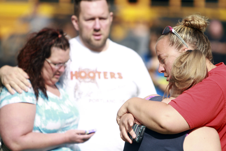 Photo - People comfort each other as they await word about the safety of students after a shooting at Reynolds High School Tuesday, June 10, 2014, in Troutdale, Ore. A gunman killed a student at the high school east of Portland Tuesday and the shooter is also dead, police said. (AP Photo/The Oregonian, Faith Cathcart)  MAGS OUT; TV OUT; LOCAL TV OUT; LOCAL INTERNET OUT; THE MERCURY OUT; WILLAMETTE WEEK OUT; PAMPLIN MEDIA GROUP OUT