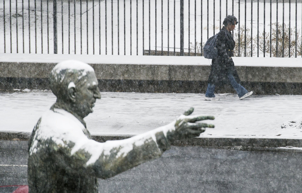 Photo - The snow covered statue of late Georgia Governor and U.S. Sen.Richard B. Russell points the direction for a pedestrian as she makes her way past the state capitol while snow begins to accumulate Tuesday, Jan. 28, 2014, in Atlanta. (AP Photo/John Amis)