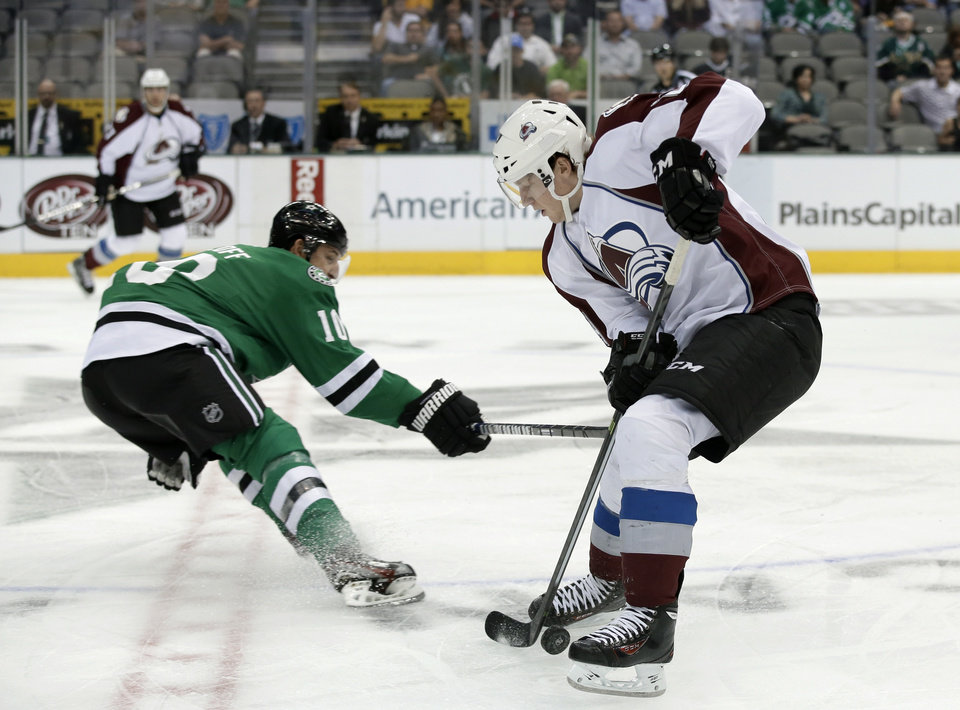 Photo - Dallas Stars center Shawn Horcoff (10) disrupts Colorado Avalanche center Nathan MacKinnon, right, as MacKinnon moves the puck upice  in the first period of a preseason NHL hockey game on Thursday, Sept. 26, 2013, in Dallas. (AP Photo/Tony Gutierrez)