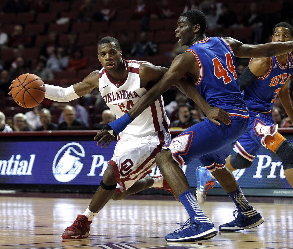 Photo - Oklahoma's Buddy Hield (24) looks to get around Texas-Arlington's Anthony Walker (44) during the men's college basketball game between the University of Oklahoma and UT-Arlington, at the LLoyd Noble Center in Norman, Okla. Tuesday, Dec. 17, 2013. Photo by Sarah Phipps, The Oklahoman
