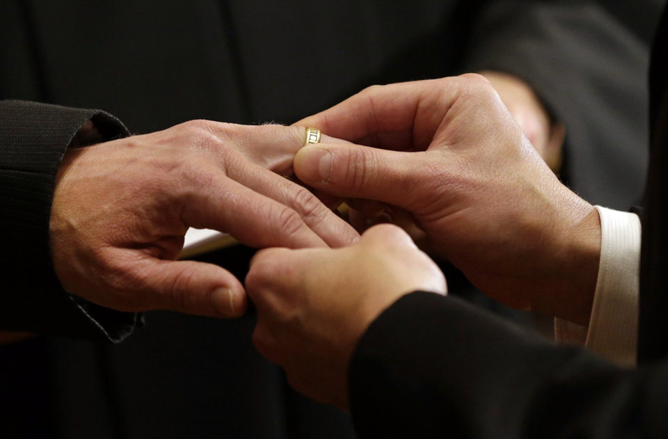 Photo - Thomas Rabe, right, places a wedding ring on Robert Coffman's finger during a marriage ceremony at City Hall in Baltimore, Tuesday, Jan. 1, 2013. Same-sex couples in Maryland are now legally permitted to marry under a new law that went into effect after midnight on Tuesday. Maryland is the first state south of the Mason-Dixon Line to approve same-sex marriage. (AP Photo/Patrick Semansky)