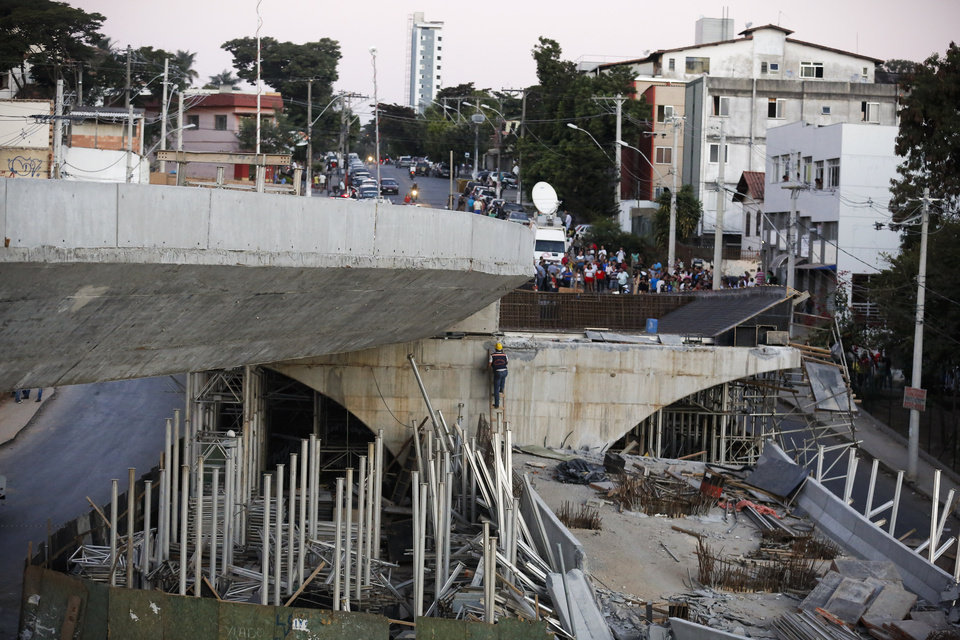 Photo - A woker walks up a ladder on a bridge that collapsed in Belo Horizonte, Brazil, Thursday, July 3, 2014. The overpass under construction collapsed Thursday in the Brazilian World Cup host city. The incident took place on a main avenue, the expansion of which was part of the World Cup infrastructure plan but, like most urban mobility projects related to the Cup, was not finished on time for the event. (AP Photo/Victor R. Caivano)