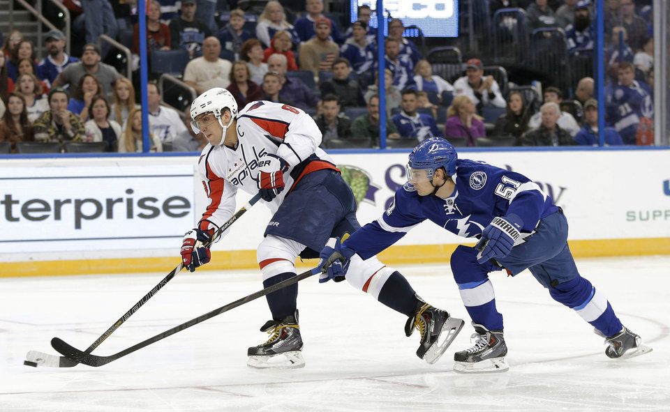 Photo - Washington Capitals right wing Alex Ovechkin (8), of Russia, fires the puck on goal after getting past Tampa Bay Lightning center Valtteri Filppula (51), of Finland, during the first period of an NHL hockey game Thursday, Jan. 9, 2014, in Tampa, Fla. (AP Photo/Chris O'Meara)