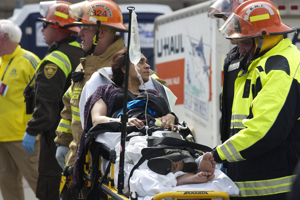 Emergency responders aid a woman on a stretcher who was injured in a bomb blast near the finish line of the Boston Marathon Monday, April 15, 2013 in Boston. Two bombs exploded in the packed streets near the finish line of the marathon on Monday, killing at least two people and injuring more than 80, authorities said. (AP Photo/Jeremy Pavia) ORG XMIT: NY119
