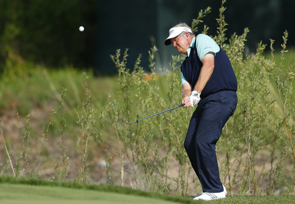 Photo - Colin Montgomerie chips onto the 17th green during the third round of the 75th Senior PGA Championship golf tournament at Harbor Shores Golf Club in Benton Harbor, Mich., Saturday, May 24, 2014. (AP Photo/Paul Sancya)
