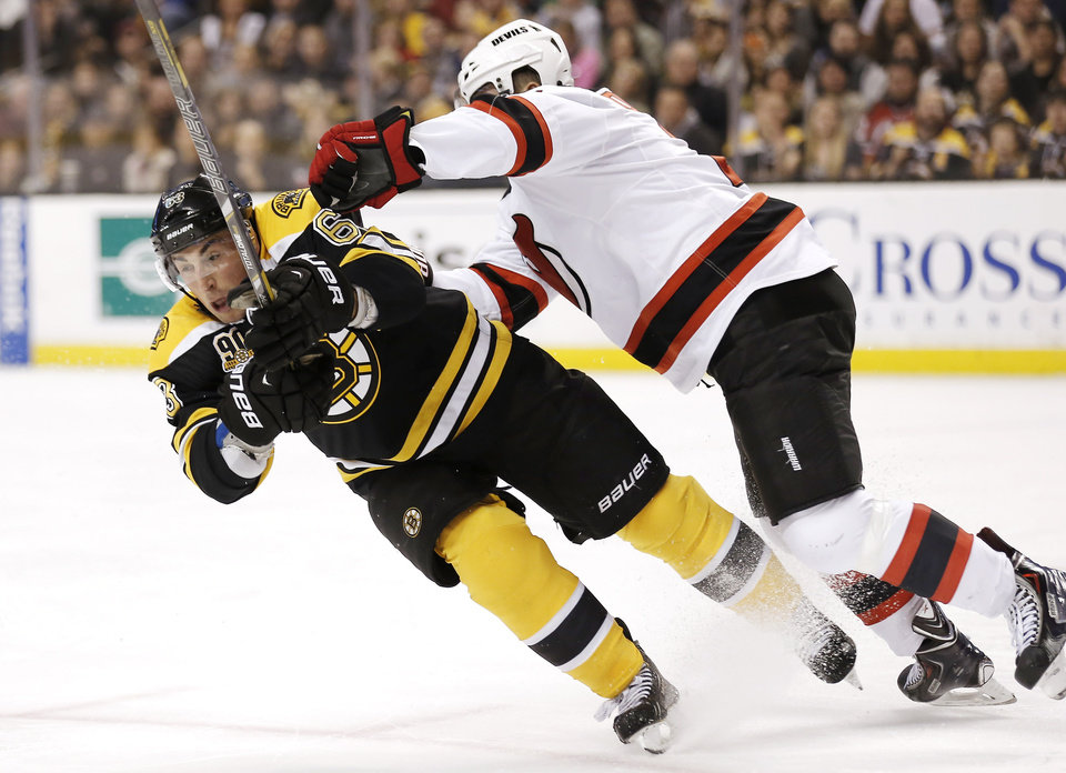 Photo - Boston Bruins' Brad Marchand, left, is checked by New Jersey Devils' Marek Zidlicky, of the Czech Republic, during the second period of an NHL hockey game in Boston, Saturday, Oct. 26, 2013. (AP Photo/Winslow Townson)