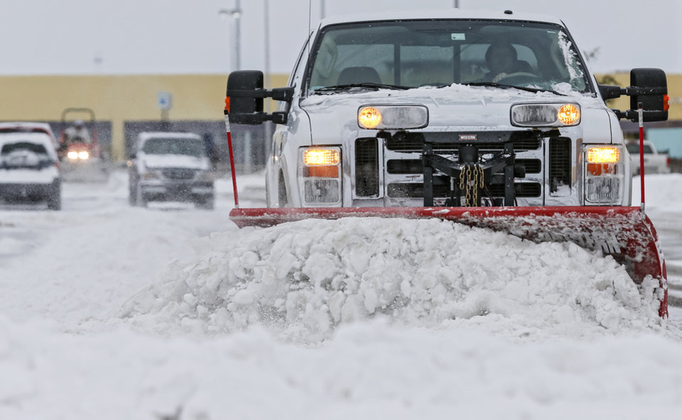 Crews work to clear the snow from the parking lot of The Outlet Shoppes at Oklahoma City in Oklahoma City, Okla. on Friday, Dec. 6, 2013. Photo by Chris Landsberger, The Oklahoman