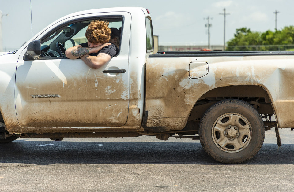 Photo - Tornado victim Raymond Gallion waits in his truck to get clearance from authorities  to collect items from his home that was hit but the tornado inside the Skyview Mobile Home Park in El Reno, Okla. on Monday, May 27, 2019. The EF3 tornado hit the area on Saturday night killing two people and injuring many others. [Chris Landsberger/The Oklahoman]
