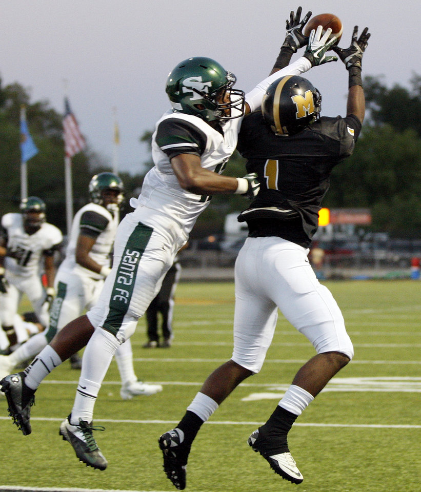 Midwest City's Cedric Fair (1) grabs a touchdown catch against Edmond Santa Fe's Dhaniel Bly (13) during the high school football game between Midwest City and Edmond Santa Fe at Rose Field in Midwest City, Okla., Thursday, Aug. 30, 2012. Photo by Nate Billings, The Oklahoman