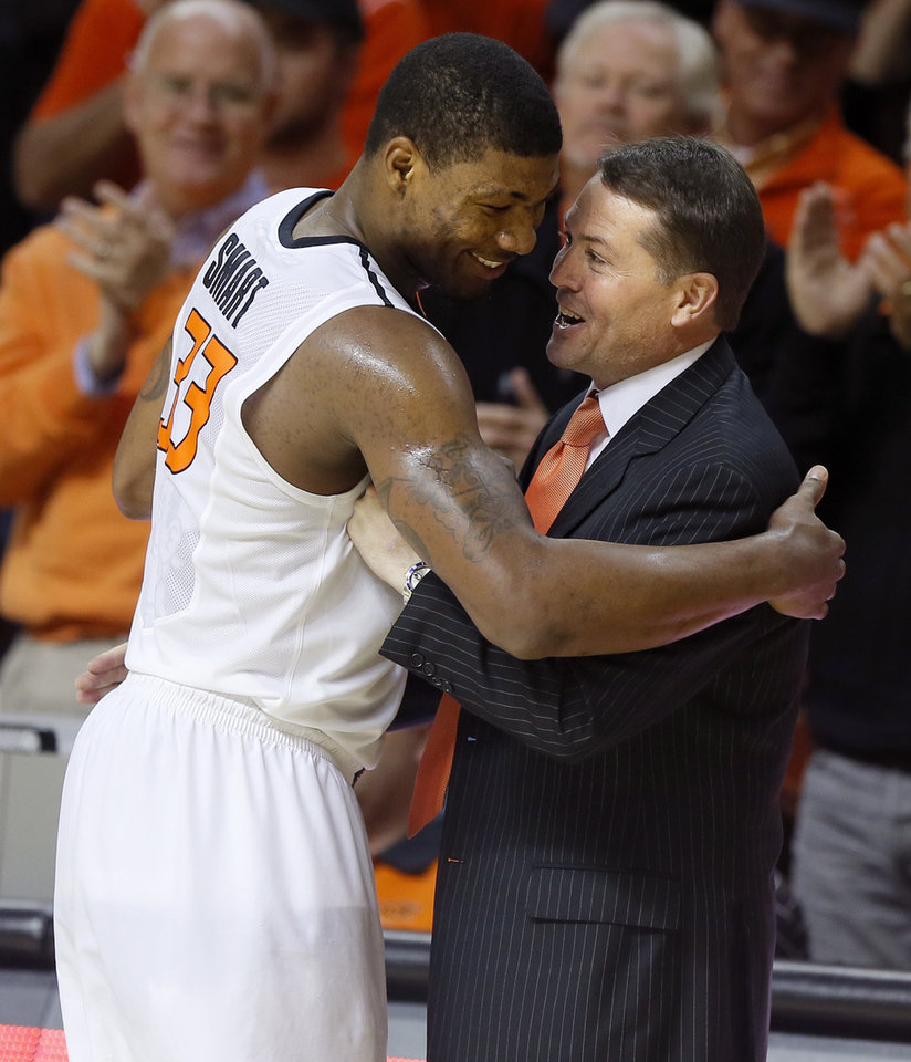 Photo - Oklahoma State's Marcus Smart (33) is greeted by coach Travis Ford as he exits the game during an NCAA college basketball game between Oklahoma State and Memphis at Gallagher-Iba Arena in Stillwater, Okla., Tuesday, Nov. 19, 2013. Photo by Bryan Terry, The Oklahoman