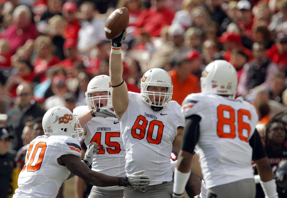 Photo - Oklahoma State's Cooper Bassett (80) celebrates an interception with teammates Markelle Martin (10), Caleb Lavey (45) and Wilson Youman during a college football game between Texas Tech University (TTU) and Oklahoma State University (OSU) at Jones AT&T Stadium in Lubbock, Texas, Saturday, Nov. 12, 2011.  Photo by Sarah Phipps, The Oklahoman  ORG XMIT: KOD