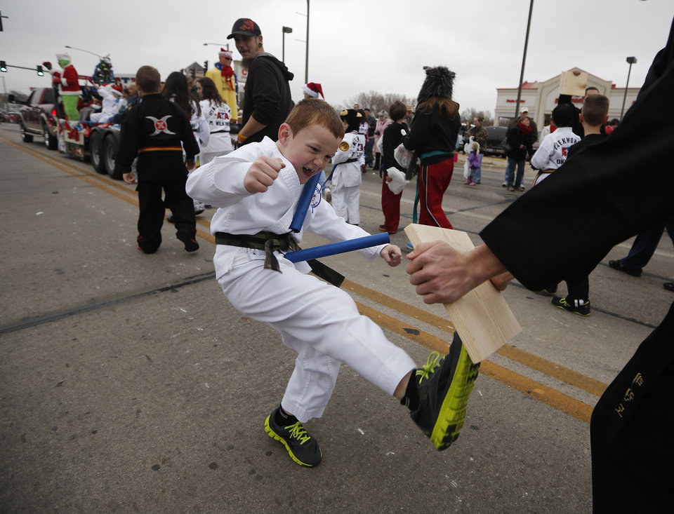 Garrett Riley, 6, demonstrates a karate kick Saturday in the Holiday Christmas Parade in downtown Norman. PHOTO BY GARETT FISBECK, FOR THE OKLAHOMAN <strong>GARETT FISBECK</strong>