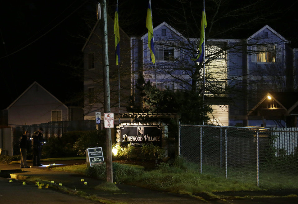 Photo - Police officers walk near evidence markers placed at the scene of an overnight shooting that left five people dead, Monday, April 22, 2013, at the Pinewood Village apartment complex in Federal Way, Wash. (AP Photo/Ted S. Warren)