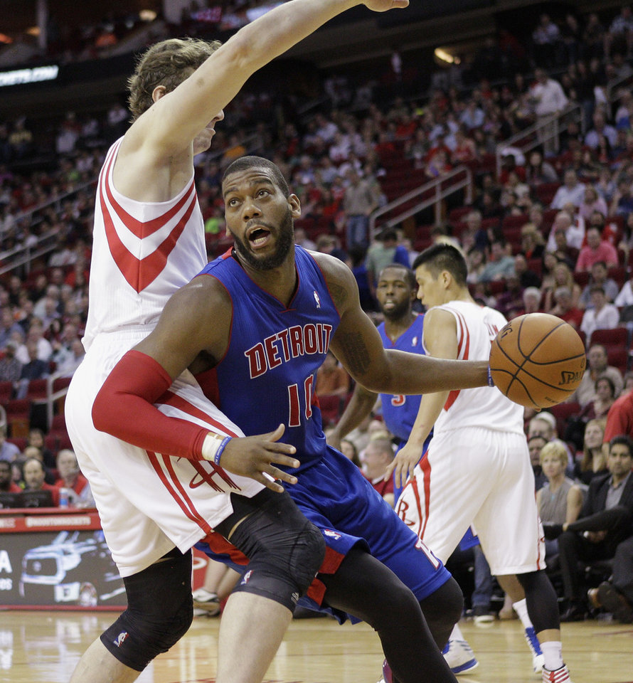 Photo - Detroit Pistons forward Greg Monroe (10) drives to the basket around Houston Rockets' Omer Asik during the first half of an NBA basketball game, Saturday, March 1, 2014, in Houston. (AP Photo/Bob Levey)
