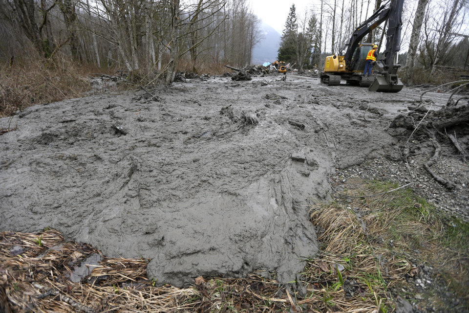 Photo - Thick, oozing mud is cleared from Washington Highway 530 by workers using heavy equipment, Tuesday, March 25, 2014, on the western edge of the massive mudslide that struck the area Saturday, killing at least 14 people and leaving dozens missing, near Arlington, Wash. (AP Photo/Ted S. Warren, Pool)
