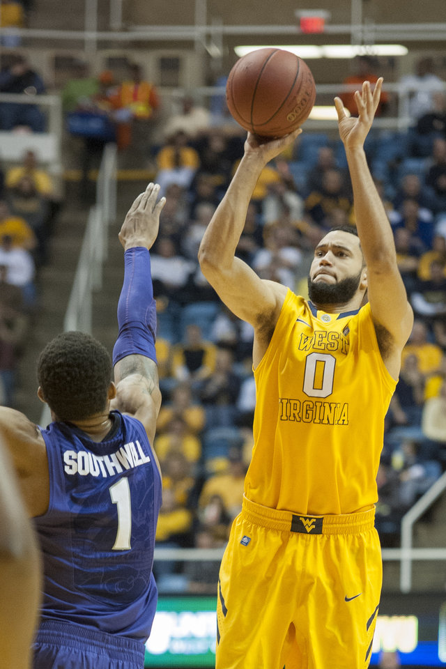 Photo - West Virginia's Remi Dibo, right, looks to shoot as Kansas State's Shane Southwell defends during the second half of an NCAA college basketball game Saturday, Feb. 1, 2014, in Morgantown, W.Va. West Virginia won 81-71. (AP Photo/Andrew Ferguson)