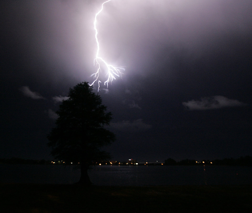 Photo - Lightning emerges from a storm cloud over Clear Lake illuminating a lone cypress tree Wednesday June 12, 2013 in LaPorte, Ind. A massive line of storms packing hail, lightning and tree-toppling winds rolled through the Midwest Wednesday evening driving people into basements for shelter, tearing down power lines and causing flooding in low-lying areas. (AP Photo/The LaPorte Herald-Argus, Bob Wellinski)