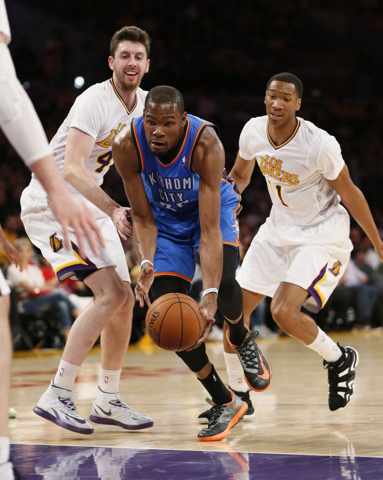 Photo - Oklahoma City Thunder small forward Kevin Durant, center, takes the ball between Los Angeles Lakers power forward Ryan Kelly, left, and small forward Wesley Johnson, right, during the first half of an NBA basketball game in Los Angeles, Sunday, March 9, 2014. (AP Photo/Danny Moloshok)